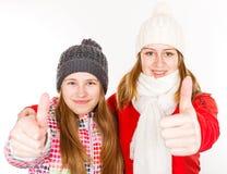Jeunes soeurs heureuses montrant des pouces  Images libres de droits