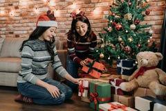 Jeunes soeurs mettant des cadeaux sous l'arbre de Noël image stock