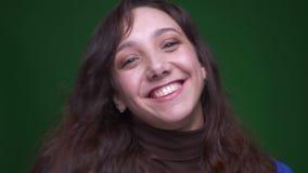 Jeunes sourires d'étudiante de brune étant joyeux heureux dans la caméra sur le fond vert banque de vidéos