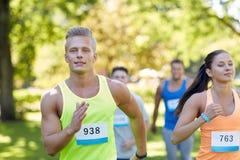 Jeunes sportifs heureux emballant des nombres d'insigne d'esprit Photos stock