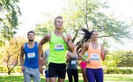 Jeunes sportifs heureux emballant des nombres d'insigne d'esprit Images stock