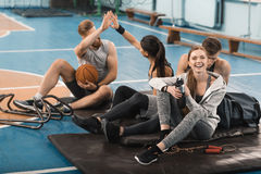 Jeunes sportifs s'asseyant sur des tapis et parlant dans la salle de gymnastique Photos stock