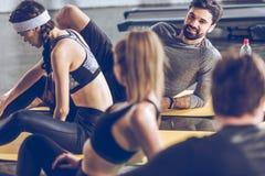Jeunes sportifs se trouvant sur des tapis de yoga et parlant tout en s'exerçant au gymnase Photo libre de droits