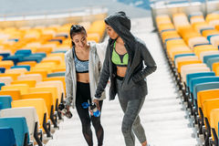 Jeunes sportives avec des bouteilles de sport sur des escaliers de stade Photographie stock