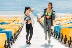 Jeunes sportives avec des bouteilles de sport sur des escaliers de stade Photo stock