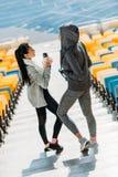 Jeunes sportives avec des bouteilles de sport sur des escaliers de stade Image stock