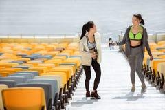 Jeunes sportives avec des bouteilles de sport sur des escaliers de stade Photographie stock libre de droits