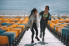 Jeunes sportives avec des bouteilles de sport sur des escaliers de stade Images stock
