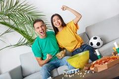 Jeunes supporters de couples observant l'équipe encourageante de match activement Photographie stock
