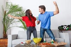 Jeunes supporters de couples observant la victoire d'équipe de match Photographie stock libre de droits