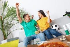 Jeunes supporters de couples observant le travail d'équipe de match Photographie stock