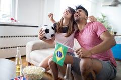 Jeunes supporters de couples regardant la rencontre à la télévision Photos libres de droits