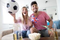 Jeunes supporters de couples regardant la rencontre à la télévision Image stock