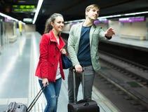 Jeunes touristes avec des valises attendant le train Image libre de droits