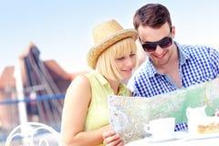Jeunes touristes avec une carte dans un café Photographie stock libre de droits