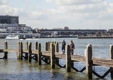 Jeunes touristes de couples regardant et indiquant le port de ville de Rotterdam, futur concept d'architecture, mode de vie indus Photographie stock