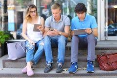 Jeunes trois amis reposant le plancher dans la rue, parlant, employant Images stock