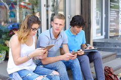 Jeunes trois amis reposant le plancher dans la rue, parlant, employant Photographie stock libre de droits