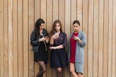 Jeunes trois femmes causant aux téléphones portables tout en se tenant ensemble dehors sur le fond en bois de mur avec le secteur Photographie stock libre de droits