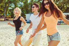 Jeunes types drôles dans des lunettes de soleil sur la plage Amis ensemble Images libres de droits