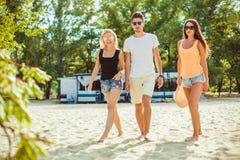 Jeunes types drôles dans des lunettes de soleil sur la plage Amis ensemble Image stock