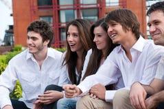 Jeunes types et filles s'asseyant ensemble Photographie stock libre de droits
