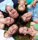 Jeunes types et filles se trouvant sur l'herbe recherchant Image stock