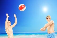 Jeunes types jouant avec une boule, à côté d'une mer Photos stock