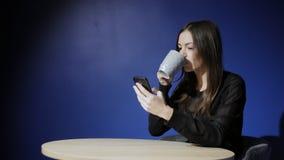 Jeunes utilisant le smartphone, passant en revue, lisant, causant et boire du café banque de vidéos