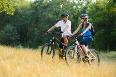 Jeunes vélos de montagne heureux d'équitation de couples extérieurs image libre de droits