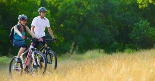 Jeunes vélos de montagne heureux d'équitation de couples extérieurs Photo stock