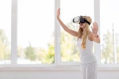 Jeunes verres blonds de Digital de réalité virtuelle d'usage de femme, belle fille de sourire heureuse Image stock