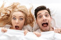 Jeunes visages affectueux choqués de bâche de couples sous la couverture Images stock