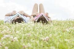 Jeunes visages décontractés de bâche de couples avec des livres tout en se trouvant sur l'herbe Photographie stock libre de droits