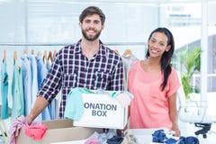 Jeunes volontaires de sourire d'amis séparant des vêtements Photographie stock libre de droits