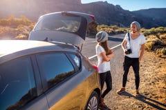 Jeunes voyageurs de couples ayant l'amusement près de la voiture Images stock