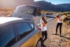 Jeunes voyageurs de couples ayant l'amusement près de la voiture Photos libres de droits