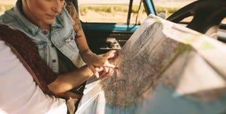 Jeunes voyageurs sur un voyage par la route regardant la carte Photographie stock