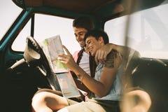 Jeunes voyageurs sur un voyage par la route regardant la carte Photos stock