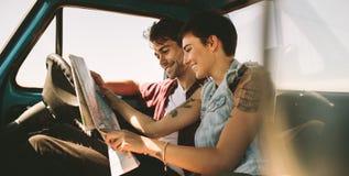 Jeunes voyageurs sur un voyage par la route regardant la carte Photo libre de droits