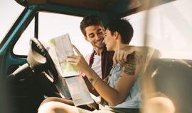 Jeunes voyageurs sur un voyage par la route regardant la carte Image stock