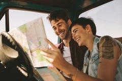 Jeunes voyageurs sur un voyage par la route regardant la carte Images stock