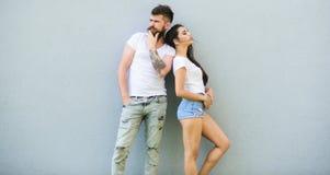 Jeunesse élégante de couples Caresse blanche de chemises de couples La fille barbue et élégante de hippie traînent romantique urb image libre de droits