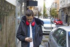 Jeunesse avec des écouteurs descendant la rue photographie stock