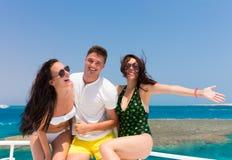 Jeunesse ayant l'amusement et la position sur le yacht à un jour d'été ensoleillé Images libres de droits
