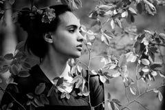 Jeunesse, beauté fille avec la fleur dans les cheveux dans des feuilles vertes photo libre de droits