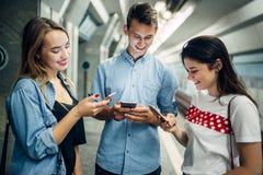 Jeunesse d'intoxiqué de téléphone utilisant des instruments dans le souterrain image stock