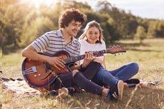 Jeunesse, datation et concept de temps de récréation L'amie et l'ami heureux s'asseyent sur l'herbe verte, jouent la guitare, app Photo stock