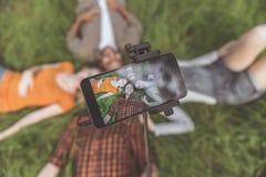 Jeunesse gaie se photographiant sur l'herbe Image stock