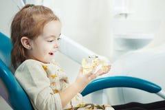 Jeux d'enfant avec la mâchoire humaine artificielle dans la chaise de dentiste images stock